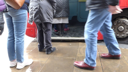 The picture shows a red bus with it's door open, four people's legs in the queue, one lady clearly in jeans and a gentleman in front of her with dark grey trousers on. A man also in jeans is crossing in front of the photo. The bus's front steps overhangs on the curb awkwardly with a ten inch gap
