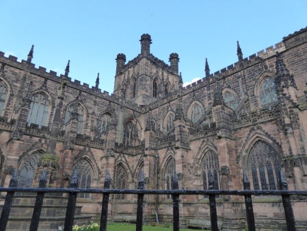 The side of Chester Cathedral at a corner. A cast iron fence in the foreground at the bottom of the screen, with a bit of green garden between that and the building. The building is mostly a dirty brown. On the bottom floor is 8 glass windows, the second floor shows 10 glass windows, with spires obstructing their view. Above those windows are more spires and the top is the tower bellfry with three chimneys showing